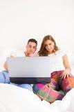 Junte sentarse de lado a lado en la cama que se relaja con el ordenador Foto de archivo