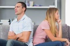 Junte sentarse de nuevo a la parte posterior después de una lucha en el sofá Foto de archivo libre de regalías