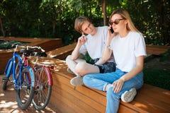 Junte sentarse en banco en parque con cerca rojas y azules las bicicletas Sentada cansada joven del hombre y cuidadosamente mirad Imagenes de archivo