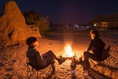 Junte sentarse en el fuego ardiente del campo en la noche El acampar en el desierto con los elefantes salvajes en fondo Aventuras Foto de archivo
