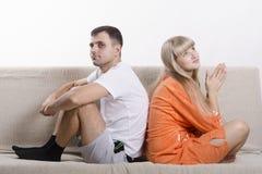 Junte sentarse en el sofá con el suyo de nuevo a uno a y a sueño Foto de archivo libre de regalías