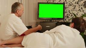 Junte sentarse en el sofá y la TV de observación con la pantalla verde almacen de video