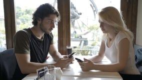Junte sentarse en la tabla del café y los mensajes que mandan un SMS en el smartphone que intercambia miradas del trastorno metrajes