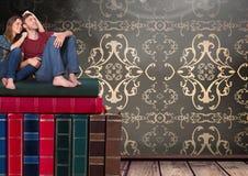 Junte sentarse en los libros apilados por la antigüedad del papel pintado decorativa Imágenes de archivo libres de regalías