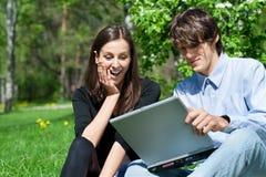 Junte sentarse en parque y usar la computadora portátil Fotografía de archivo libre de regalías