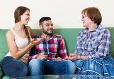 Junte sentarse en sala de estar y hablar con la madre foto de archivo