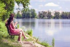 Junte sentarse en un banco al lado de un lago en un día de verano soleado Imagen de archivo