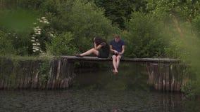 Junte sentarse en un pontón de madera en un río en verano El marido que usa una tableta y a una esposa digitales está enojado y t almacen de video