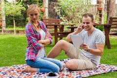 Junte sentarse en una manta en el parque del verde del verano Fotografía de archivo libre de regalías