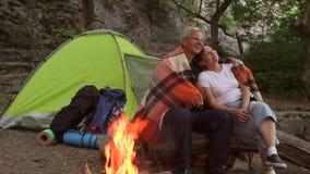 Junte sentarse por el fuego cubierto con una manta almacen de video