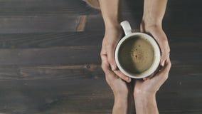 Junte sostener la taza de café en manos en el fondo de madera, visión superior almacen de metraje de vídeo