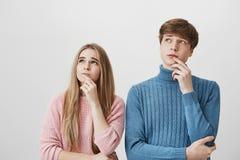 Junte sostener los fingeres en las barbillas, mirando hacia un lado de pensamiento en algo, oponiéndose a la pared gris De pelo r fotografía de archivo libre de regalías