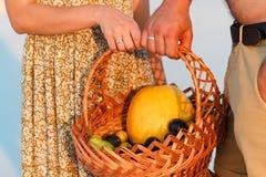 Junte sostener una cesta de mimbre con la fruta, el hombre y la mujer teniendo una comida campestre en la playa blanca de la aren Imágenes de archivo libres de regalías