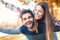 Junte tener el hombre de la diversión que da a cuestas a la mujer en parque Foto de archivo