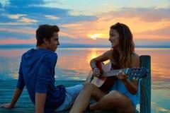 Junte tocar la guitarra en embarcadero de la puesta del sol en la playa de la oscuridad Imagen de archivo libre de regalías