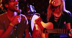 Junte tocar la guitarra y el canto de la canción en el club nocturno 4k almacen de metraje de vídeo