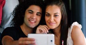 Junte tomar el selfie en el teléfono móvil en pub almacen de video