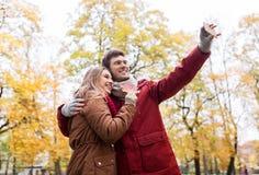 Junte tomar el selfie por smartphone en parque del otoño Fotos de archivo libres de regalías