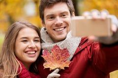 Junte tomar el selfie por smartphone en parque del otoño Foto de archivo libre de regalías