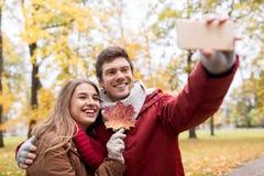 Junte tomar el selfie por smartphone en parque del otoño Imagen de archivo libre de regalías