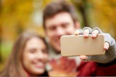 Junte tomar el selfie por smartphone en parque del otoño Imágenes de archivo libres de regalías