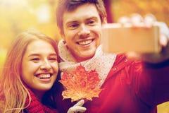 Junte tomar el selfie por smartphone en parque del otoño Fotografía de archivo