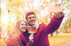 Junte tomar el selfie por smartphone en parque del otoño Imagenes de archivo