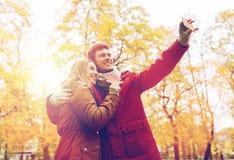 Junte tomar el selfie por smartphone en parque del otoño Foto de archivo