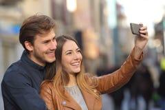 Junte tomar la foto del selfie con un teléfono elegante en la calle Fotos de archivo libres de regalías
