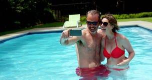 Junte tomar un selfie en el teléfono móvil en piscina metrajes