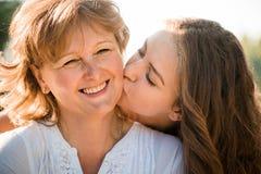 Junto - madre feliz e hija adolescente al aire libre Fotografía de archivo