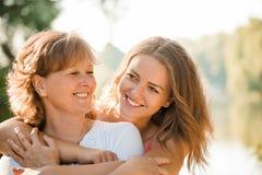 Junto - madre feliz e hija adolescente al aire libre Foto de archivo libre de regalías