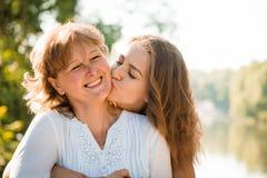 Junto - madre feliz e hija adolescente al aire libre Fotos de archivo libres de regalías