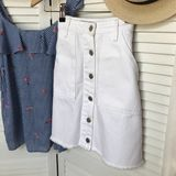 Jupe blanche avec un chemisier bleu sur le fond d'un scre blanc photographie stock