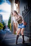 Jupe courte et sac de fille marchant sur la rue. Jeune fille européenne dans l'environnement urbain Image stock
