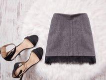 Jupe grise avec la dentelle et chaussures noires sur la fourrure blanche, concept à la mode photos stock