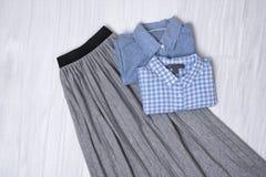 Jupe plissée grise et chemises bleues sur le fond en bois Mode image stock