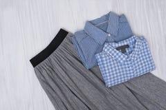 Jupe plissée grise et chemises bleues sur le fond en bois Mode photographie stock