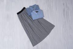 Jupe plissée grise et chemises bleues sur le fond en bois Mode image libre de droits