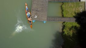 Summer vacation river jump. Juping in the river from a pier on a canoe trip, aerial drone view stock footage