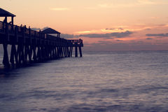 Jupiter Fishing Pier. Fishing pier in Jupiter Florda at sunrise with people fishing off it stock image
