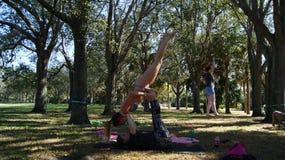 JUPITER, FLORIDA USA - 17. JUNI 2017 Junge Frauen, die acro Yoga u. slackline auf einem allgemeinen Park in Florida tun lizenzfreies stockbild