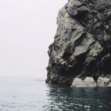 Juraküste - nackter Fels gegen das kalte Meer Stockbild