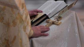 Juramento en los recienes casados en la biblia lujosamente adornada Manos de hombres en la iglesia cerca del altar, la cruz del s metrajes