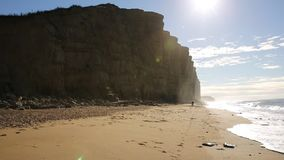 Jurassic coast Dorset at West Bay uk with sun shining on sandstone cliffs and distant man walking on beach by waves stock footage