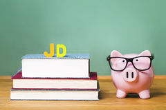 Juris Doctor law degree theme with pink piggy bank. With chalkboard in the background as concept image of the costs of education Stock Image