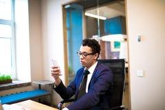 Jurista masculino bem sucedido que conversa em linha no telefone celular Gerente que usa apps no telefone de pilha fotografia de stock