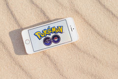 JURMALA, LATVIA - July 13, 2016: Pokemon Go logo on the smartphone. Pokemon Go is a location-based augmented reality mobile game. Phone in the sand Royalty Free Stock Photos