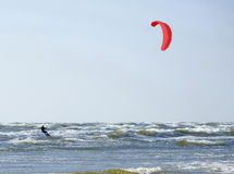 Jurmala Latvia. Surfing at the sea with a red parachute at s. Jürmala Latvia. Surfing at the sea with a red parachute at strong wind and waves. Horizontal stock photo