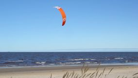 Surfing at the sea with a red parachute at strong wind and waves. kitesurfing. stock video